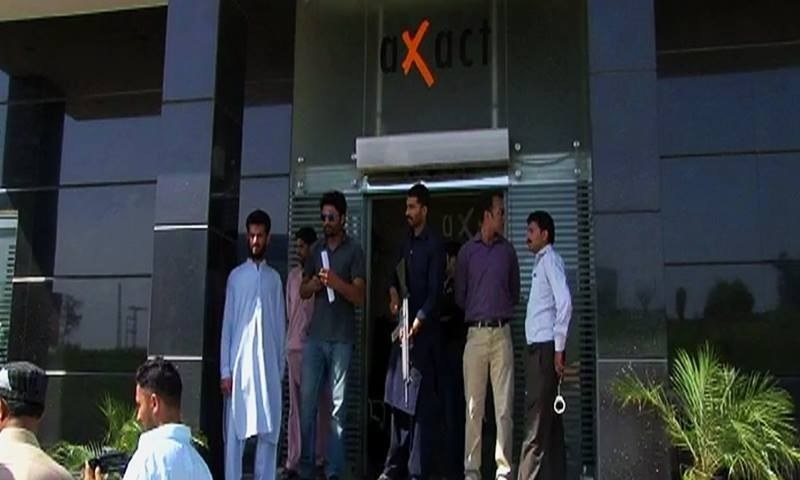 A view of people standing at the entrance of Axact's Islamabad office during the FIA's probe into allegations levelled against the IT company. — DawnNews screengrab