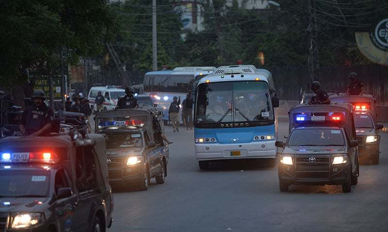 Security personnel escort buses carrying Zimbabwe and Pakistan cricket teams as they leave after attending a practice session at the Gaddafi Stadium in Lahore. — AFP