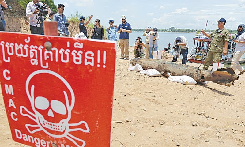 PHNOM PENH: Journalists take photographs of a bomb pulled from the murky depths of the Mekong River on Thursday.—AFP