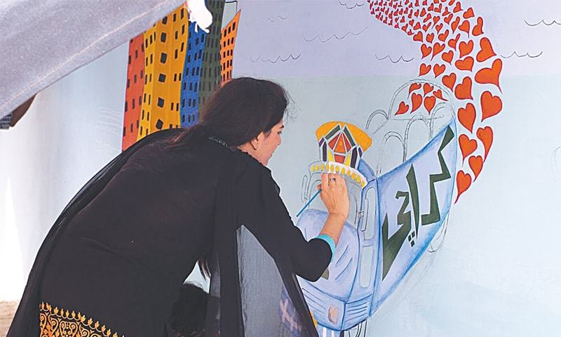 AN artist creating a painting on Thursday on a wall that was earlier smeared with assorted graffiti.—Photo by Momina Khan