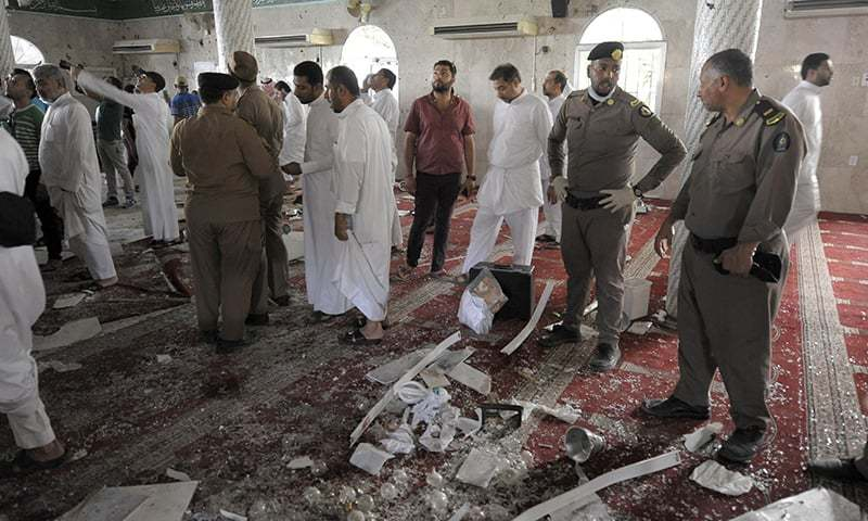 Saudi policemen gather around debris following a blast inside a mosque in Qatif. -AFP