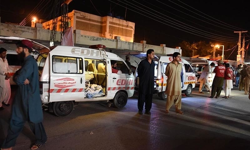 Residents gather around an ambulance carrying dead bodies of killed bus passengers outside the hospital in Quetta. — AFP Photo