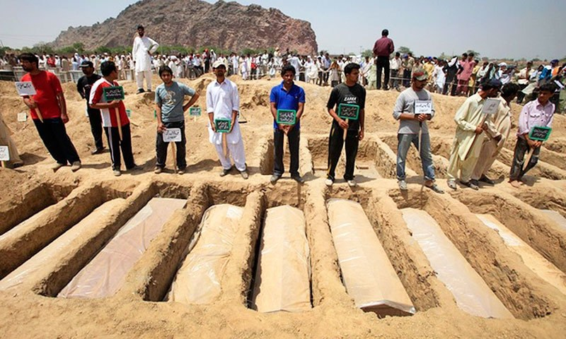 Members of the Ahmadi community hold the names of victims as they stand over their graves in on May 29, 2010. —Reuters
