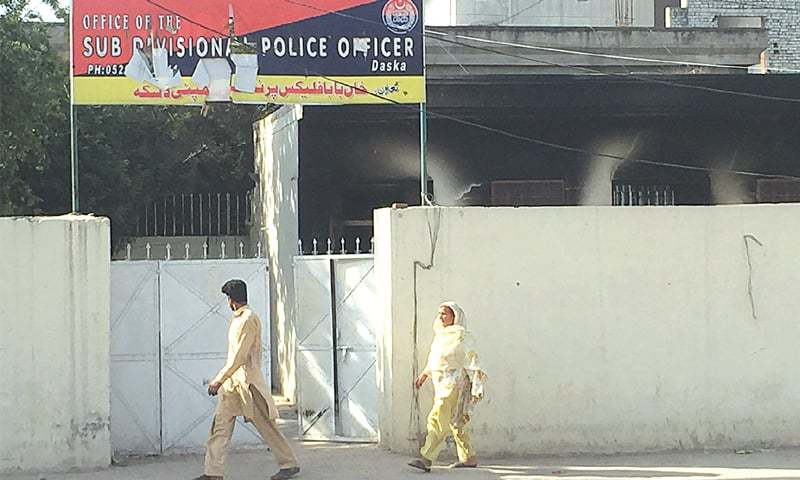 PEOPLE walk by the torched office of the sub-divisional police officer in Daska, Sialkot, where violent confrontations took place between lawyers and police on May 25.—Photo by writer