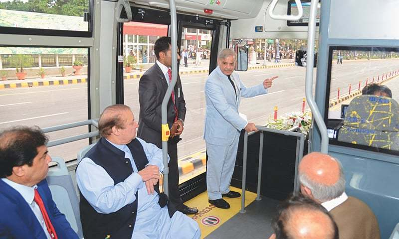Nawaz Sharif, seated in a bus, being briefed on the route of the Metro Bus Service by Shahbaz Sharif. —File