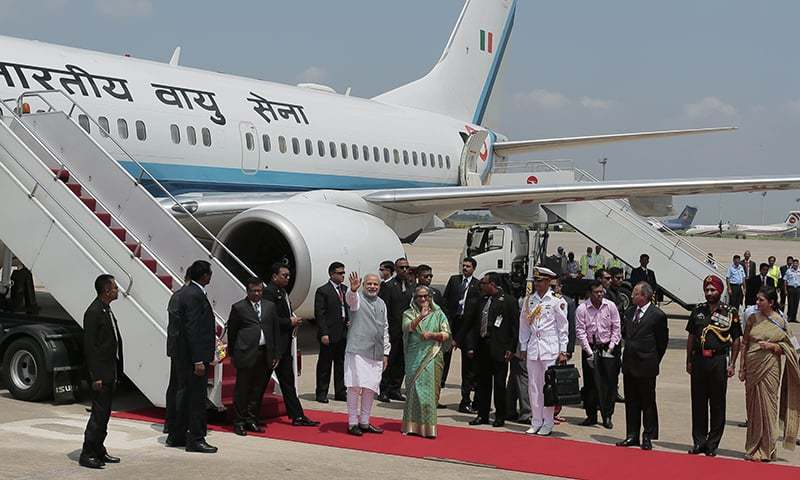 Indian Prime Minister Narendra Modi and Bangladesh's Prime Minister Sheikh Hasina wave to the media upon Modi's arrival at the Hazrat Shahjalal International airport in Dhaka, Bangladesh, Saturday, June 6, 2015. -AP