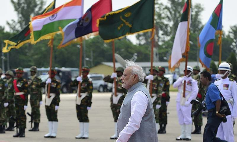 Indian Prime Minister, Narendra Modi (C) inspects the Bangladeshi guard of honour on his arrival at the Hazrat Shahjalal International Airport in Dhaka on June 6, 2015. -AFP
