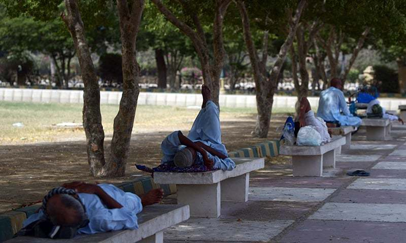 Men rest in the shade of trees during a heatwave in Karachi. —AFP