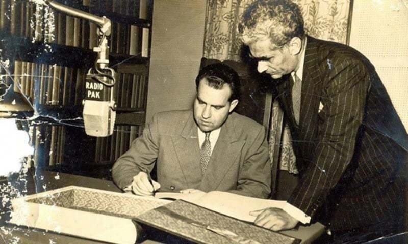 In 1950s, US Vice-President Richard Nixon signs a guestbook at Radio Pakistan, Karachi, as Z.A. Bukhari looks on. —Creative commons