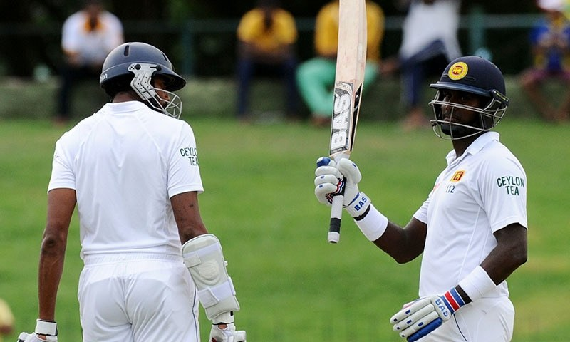 Sri Lankan cricket captain Angelo Mathews (R) is watched by his teammate Jehan Mubarak (L) as he raises his bat to the crowd after scoring a half-century (50 runs) during the third day  of the third and final Test cricket match between Sri Lanka and Pakistan at the Pallekele International Cricket Stadium in Pallekele on July 5, 2015. — AFP