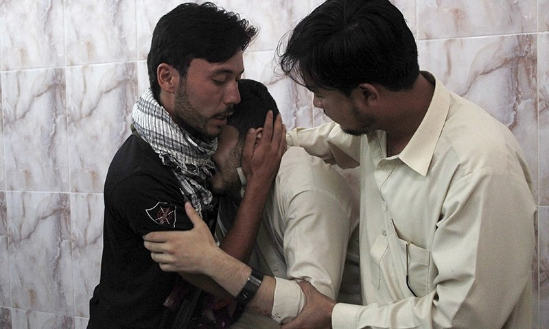 Men mourn the death of a relative, who was killed with two others by unidentified gunmen on July 6. A policeman and two others were killed when unidentified assailants opened fire on them near the passport office at Joint Road in Quetta on Monday, according to the police. —Reuters