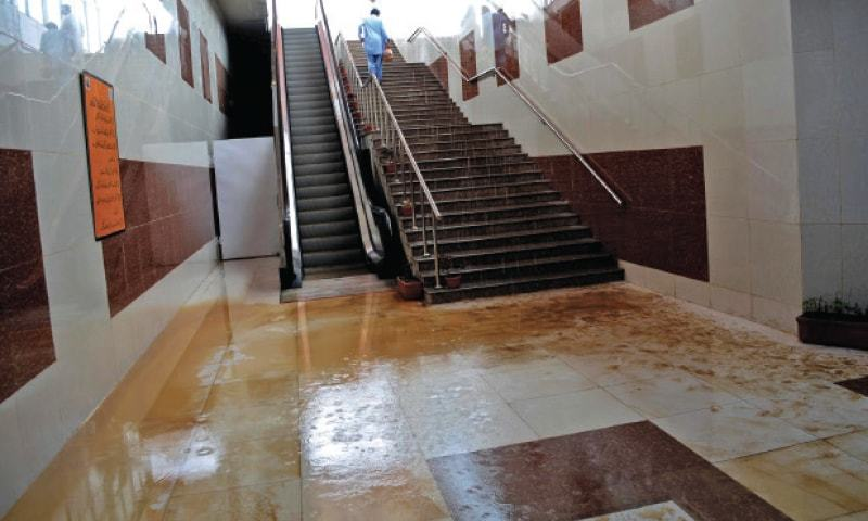 Rainwater flooded Centaurus metro bus station on Tuesday. In the other picture,  workers are seen cleaning the station. — White Star
