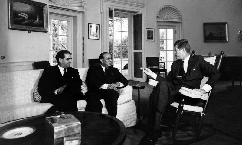امریکی صدر جان ایف کینیڈی پاکستان کے وزیرِ خارجہ محمد علی بوگرہ اور امریکا میں پاکستانی سفیر عزیز احمد کے ساتھ وہائٹ ہاؤس میں۔ 15 اکتوبر 1962 —  Abbie Rowe. White House Photographs. John F. Kennedy Presidential Library and Museum, Boston
