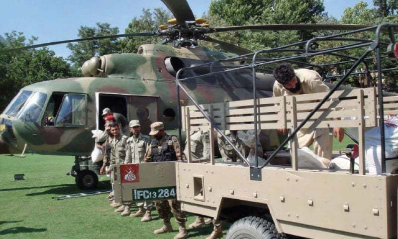 An army rescue team loads relief goods on a helicopter in Chitral for flood-affected people. — APP