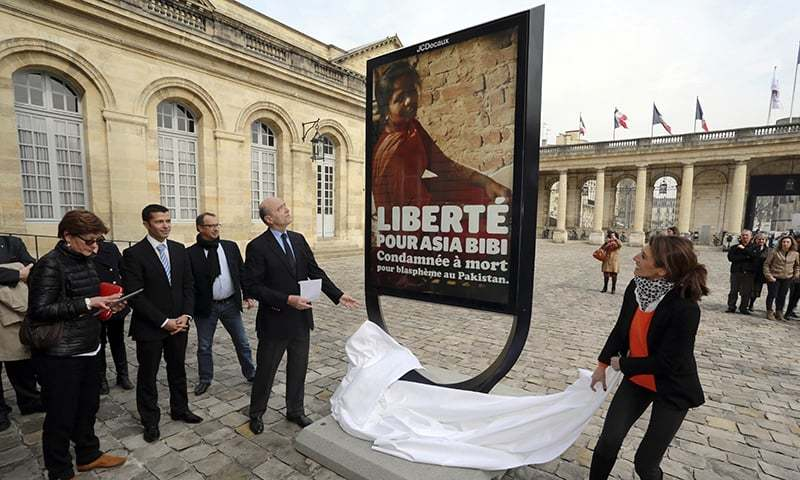 Mayor Alain Juppe (L) unveils a poster in the courtyard of the City Hall in the southwestern French city of Bordeaux in honour of Asia Bibi in March 2015. ─ AFP/File
