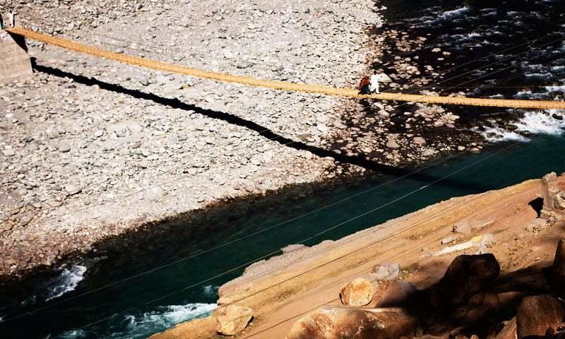 Villagers cross the Swat River on a makeshift bridge in Kalam, in Nov 2010. —AP