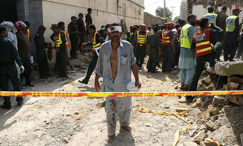 An injured man walks away as rescue workers search after a blast near the home of the home minister of Punjab province, Shuja Khanzada. —Reuters