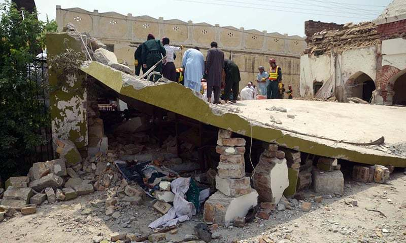 Rescue workers seen on roof of a building which collapsed after suicide attack on Shuja Khanzada who was killed in the attack. —Online