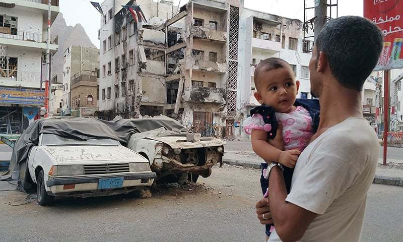 A Yemeni man carrying his daughter looks at a building destroyed during fighting against Houthi fighters in the port city of Aden. —AP/File