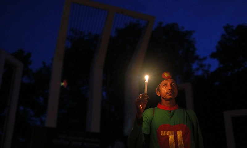 A Bangladeshi activist holds a candle, as they protest against the killing of secular bloggers in Dhaka, Bangladesh. ─ AP Photo