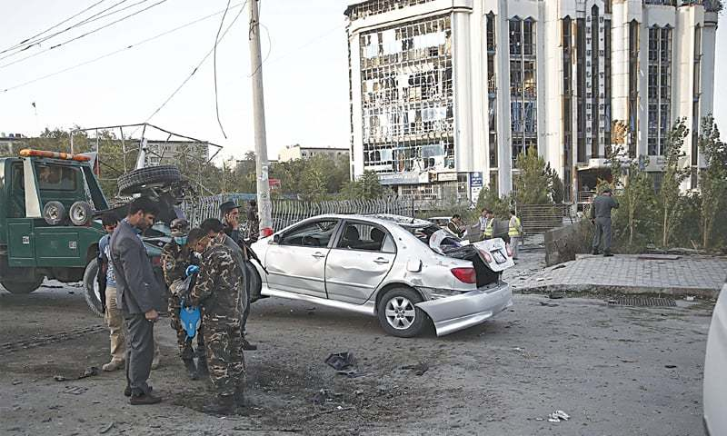 Kabul: A damaged car is being moved away from a crater caused by the bomb blast.—Reuters