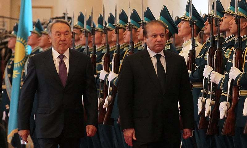 Kazakh President Nursultan Nazarbayev and Pakistani Prime Minister Nawaz Sharif review an honour guard during a welcoming ceremony in Astana. —AFP