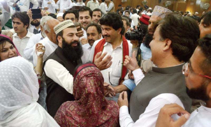 PTI workers greet Arbab Mohammad Asim Khan on his election as Peshawar district nazim. —Photo by Shahbaz Butt