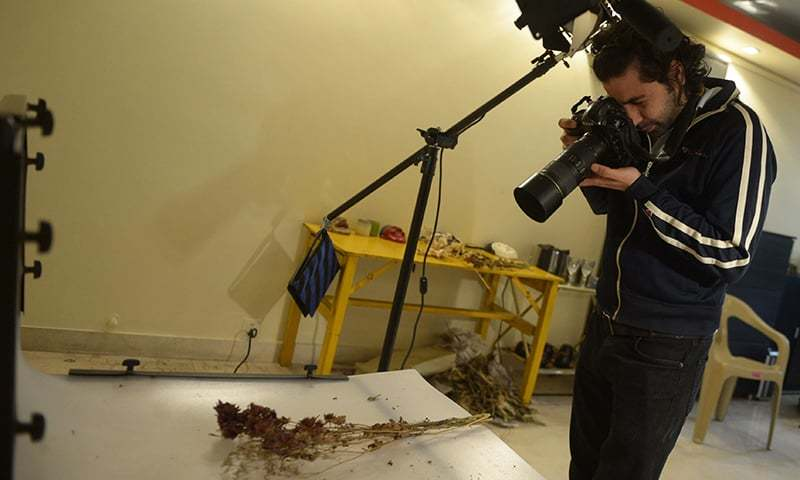 Izdeyar Setna working at his studio in Karachi. — AFP
