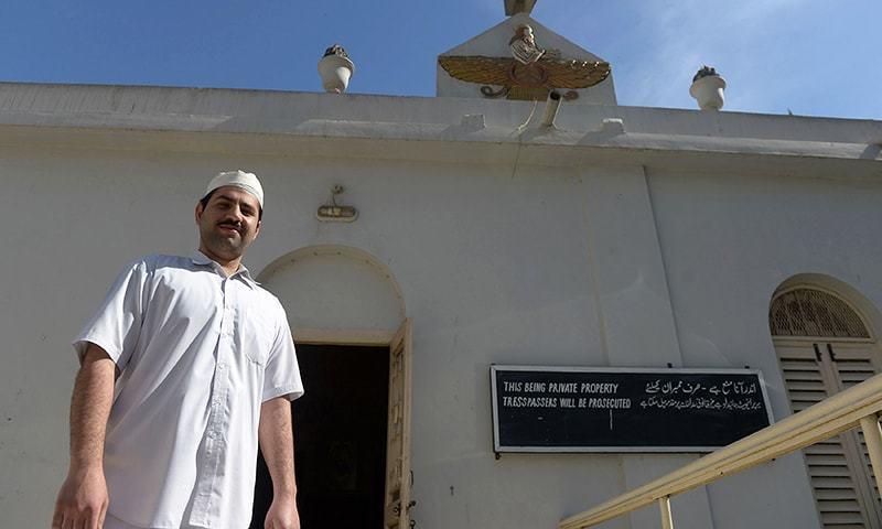 Pakistani Parsi priest walking past a temple in Karachi. — AFP
