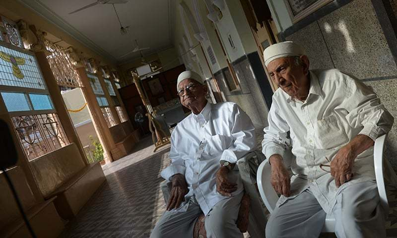 Pakistani Parsi priests Jehangir Noshik (L) and Jal Dinshaw (R) sitting at an Agyari (Fire Temple) in Karachi. — AFP