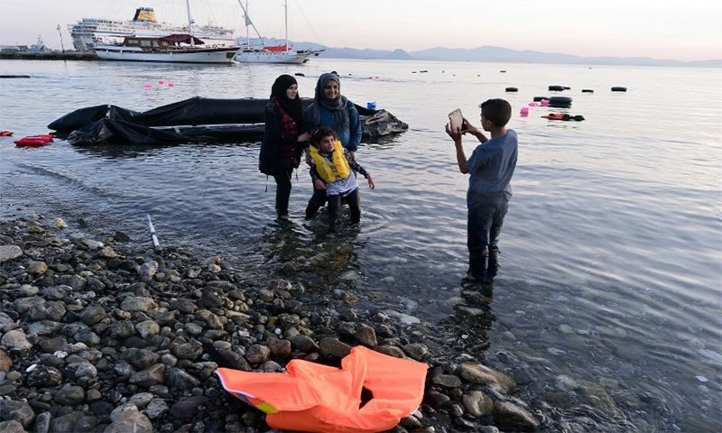 Syrian migrants take a picture after their safe arrival on an overcrowded dinghy to the coast of the southeastern Greek island of Kos from Turkey, on August 15, 2015. —AFP