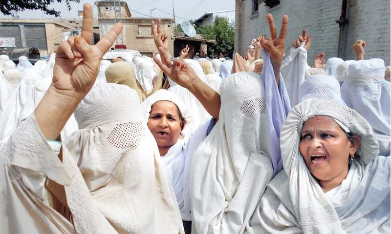 Health workers protest in front of the DHO office in Bannu on Friday. — INP