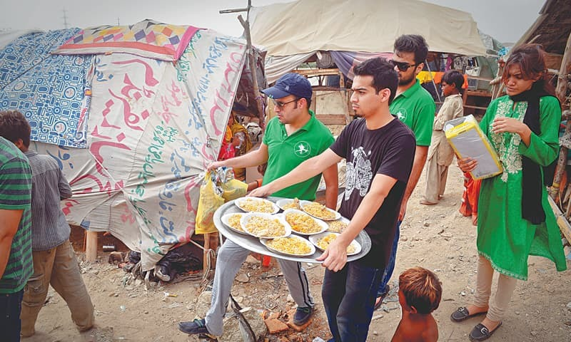 VOLUNTEERS from the Robin Hood Army come to Hijrat colony to give away food which they have collected during the week from private donors and restaurants. —Fahim Siddiqi/ White Star