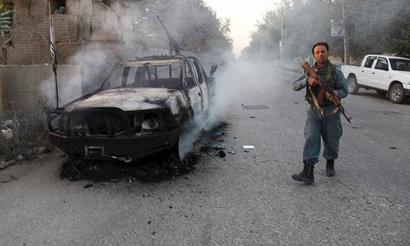 An Afghan policeman patrols next to a burning vehicle in the city of Kunduz, Afghanistan. — Reuters