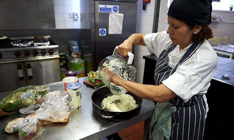 Marlith Tenazoa Del Aguila from Peru prepares food in the kitchen at Mazi Mas. ─ AFP