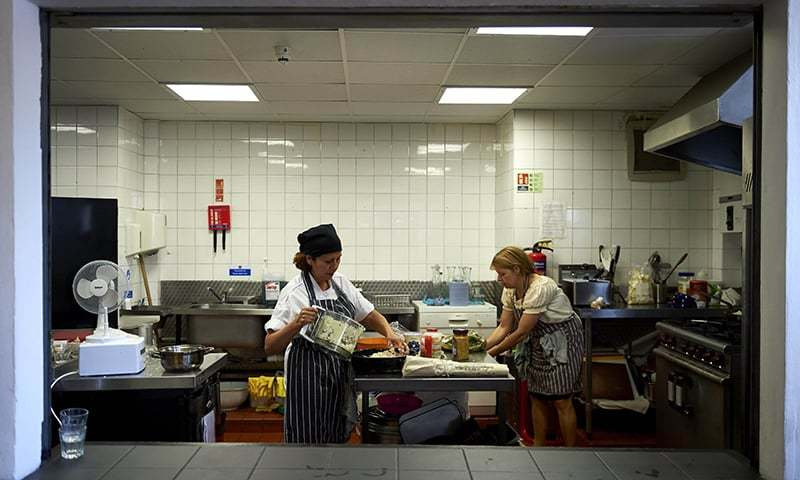 Marlith Tenazoa Del Aguila from Peru (L), and Roberta Siao from Brazil, prepare food in the kitchen at Mazi Mas restaurant. ─ AFP