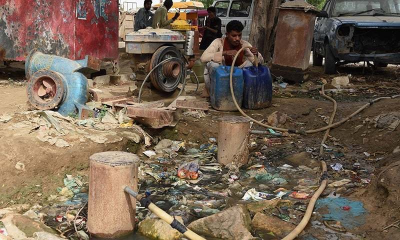 In this photograph taken on August 20, 2015, a man fills a container with water in a slum area of Karachi.  — AFP