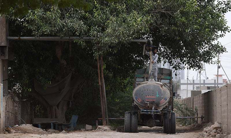 In this photograph taken on August 20, 2015, a man fills a water tanker from an illegal hydrant to provide water to residential areas in Karachi.  — AFP