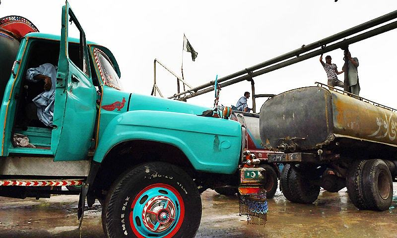 In this photograph taken on August 22, 2015, employees fill water tankers at a government hydrant to provide residential areas in Karachi. — AFP