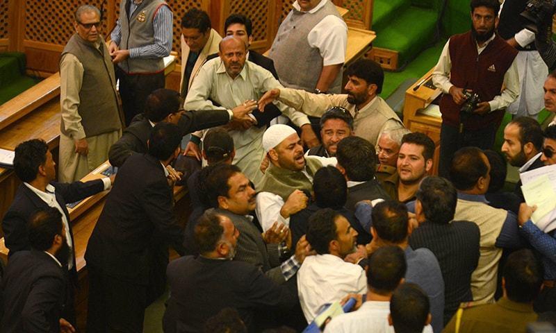 Independent lawmaker, Engineer Rashid (CL-back) shouts after being  thrashed by Bhartiya Janta Party (BJP) legislators in the legislative assembly in Srinagar on October 8, 2015.  — AFP