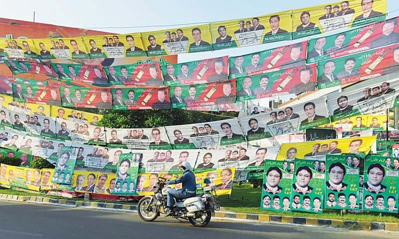 A policeman on his motorbike passes by a road decked with PTI and PML-N banners for the NA-122 by-election in Lahore on Sunday.—Arif Ali / White Star