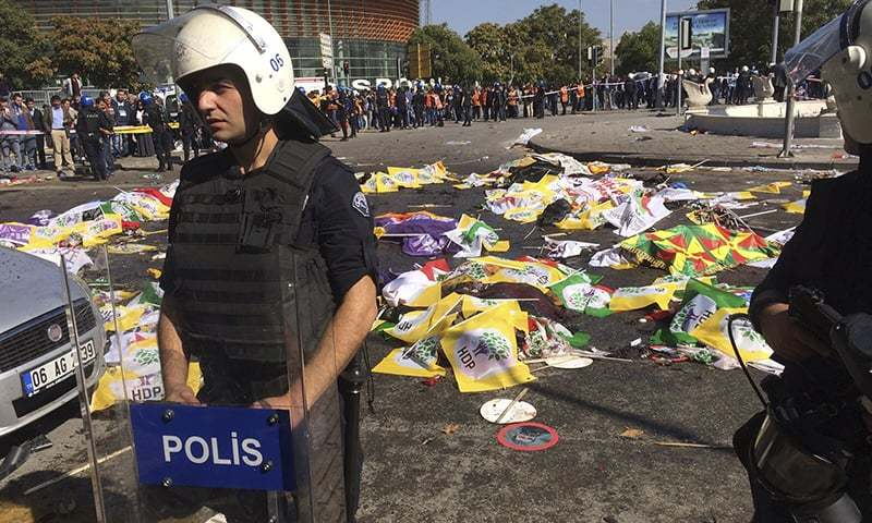 Bodies of victims are covered with flags and banners as a police officer secure the area after an explosion in Ankara, Turkey. — AP