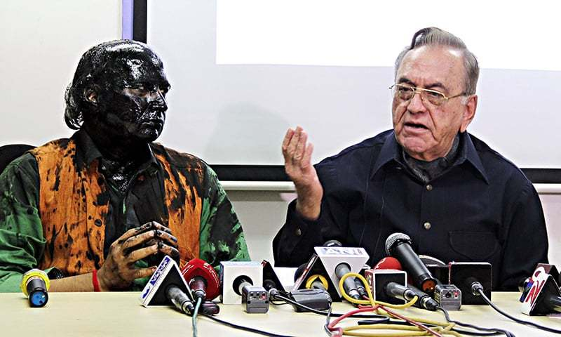 Indian activist Sudheendra Kulkarni (L), whose face was blackened by ink in an alleged attack, looks on as former Pakistani foreign minister Khurshid Mahmud Kasuri speaks to media in Mumbai on October 12, 2015. —AFP