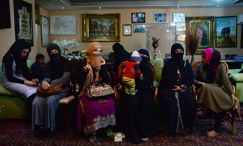 In this photograph taken on October 10, 2015,  young Afghan women, who have been displaced from the northern Afghan city of Kunduz during clashes between Afghan security forces and Taliban insurgents, speak as they gather waiting for temporary shelter donated by a businessman at a hotel in Kabul. —AFP