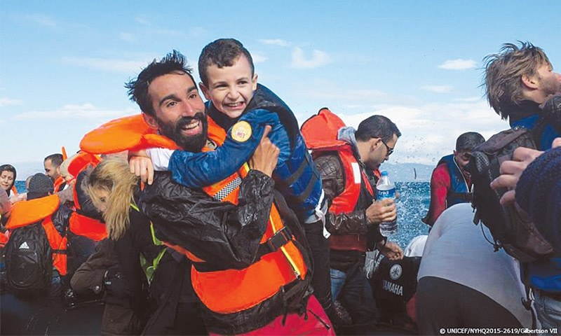 The embrace of safety: a boy laughs when Kinan takes him off the boat