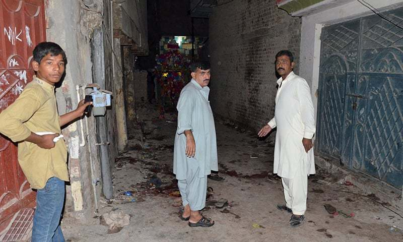 People stand at the site of a bombing in Jacobabad, Sindh. —Reuters