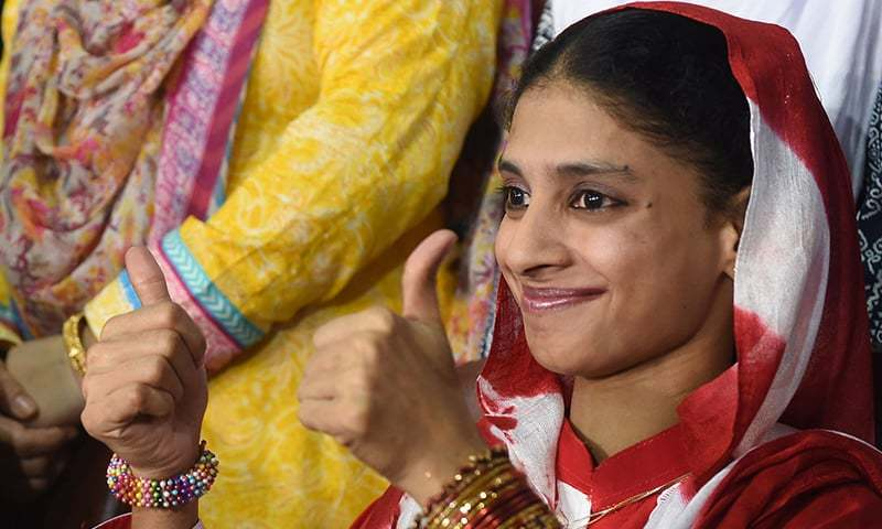 Deaf-mute Indian woman Geeta gestures to the media before leaving for the airport from the Edhi Foundation in Karachi. —AFP
