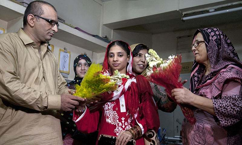 Faisal Edhi, head of Edhi Foundation, presents a bouquet  to Indian national Geeta prior her departure from Karachi. —AP