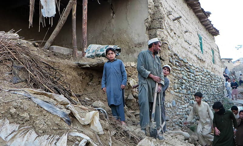 Pakistani residents gather next to the rubble of damaged house following an earthquake in Bajaur on October 26, 2015. —AFP