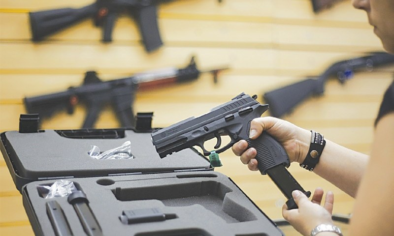 Sao Paulo (Brazil): A woman handles a pistol at a gun shop in Sao Caetano do Sul on Friday. Brazil has one of the highest murder toll on the planet.—AFP